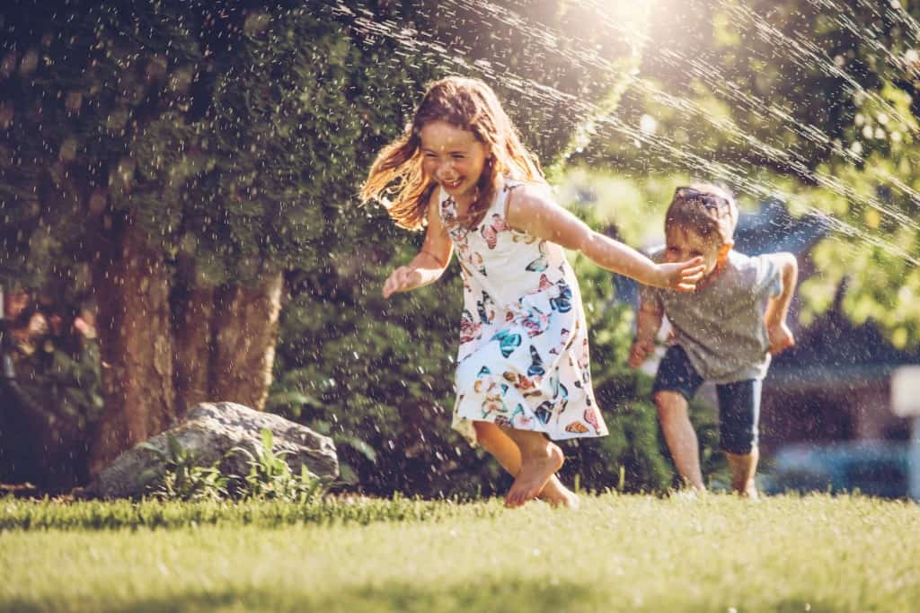 Kids happily playing with sprinkler outside.
