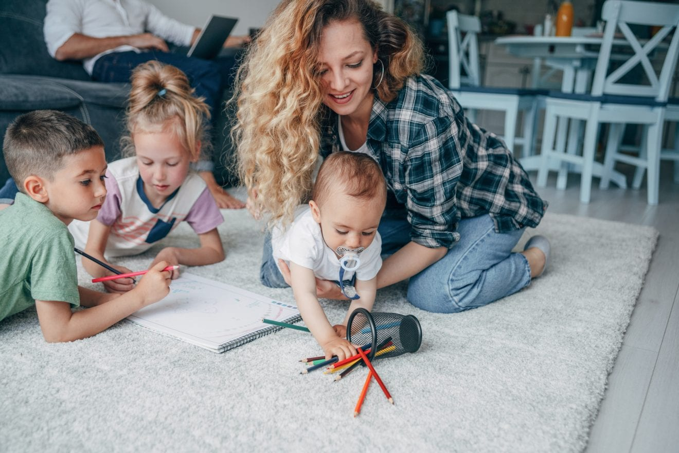 Young happy family drawing on the floor. Father working on a laptop at home.