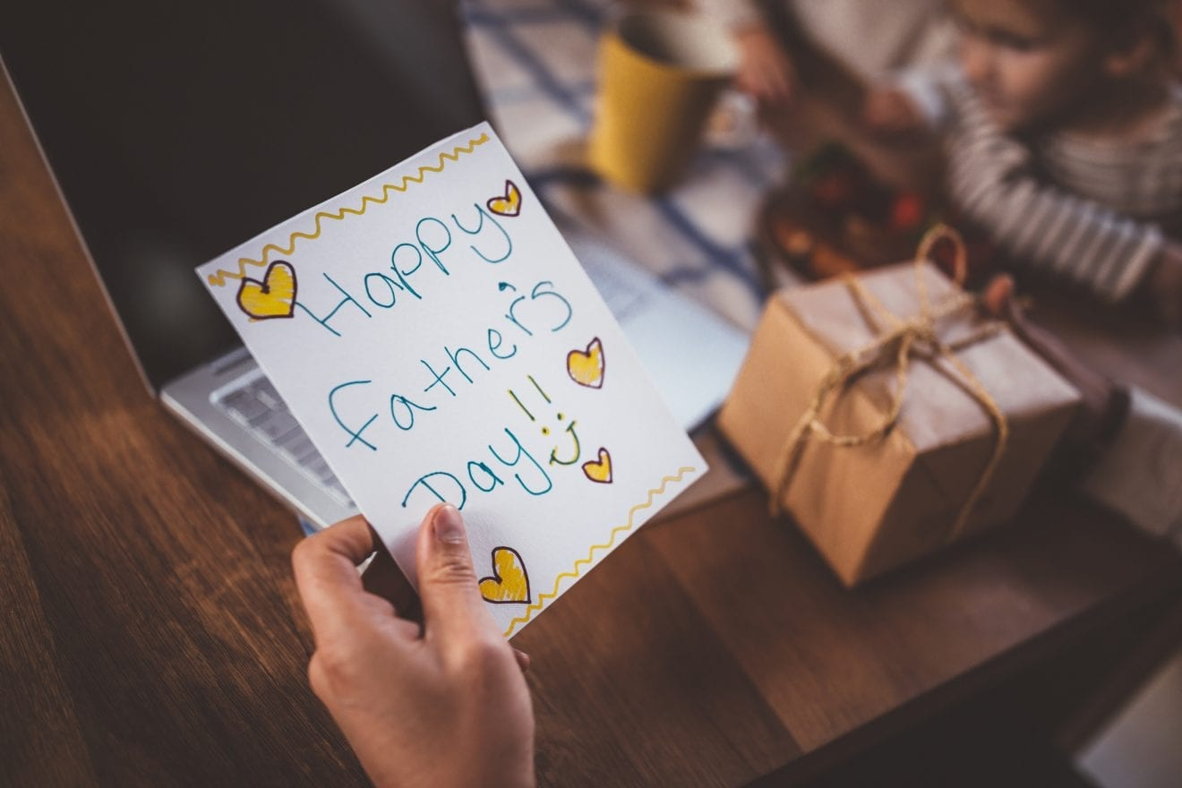 Close-up of father's hands holding handmade card and present from children on father's day