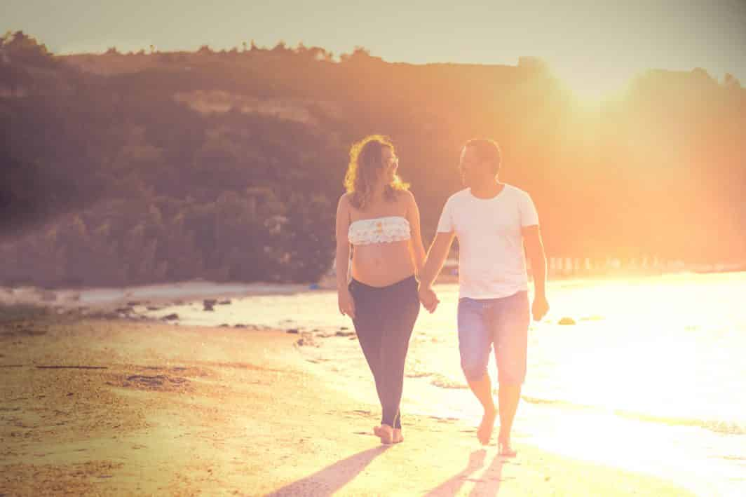 Pregnant woman and partner holding hands walking on the beach.