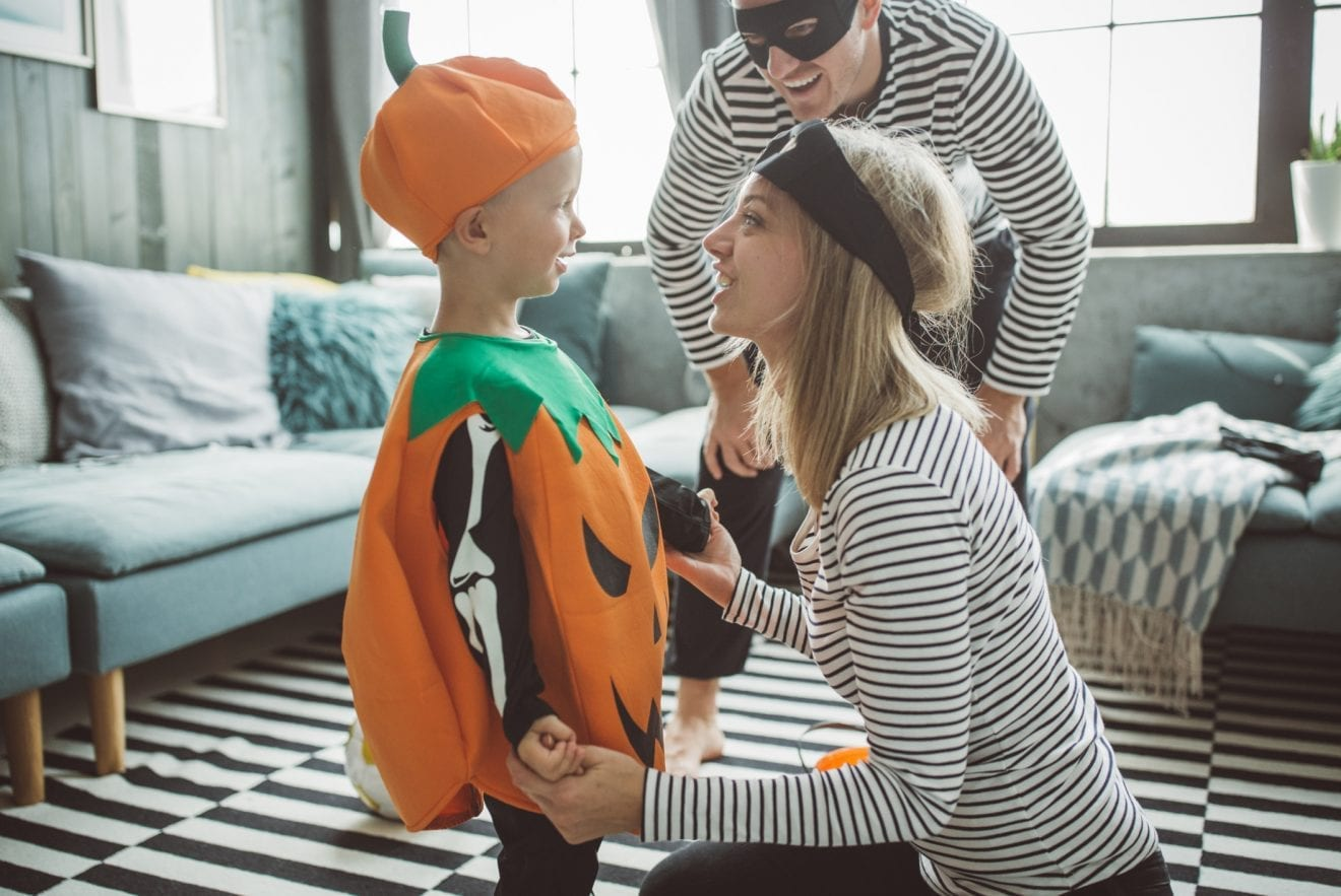 Young parents with baby boy celebrating Halloween at home. They ware costumes and playing around in living room