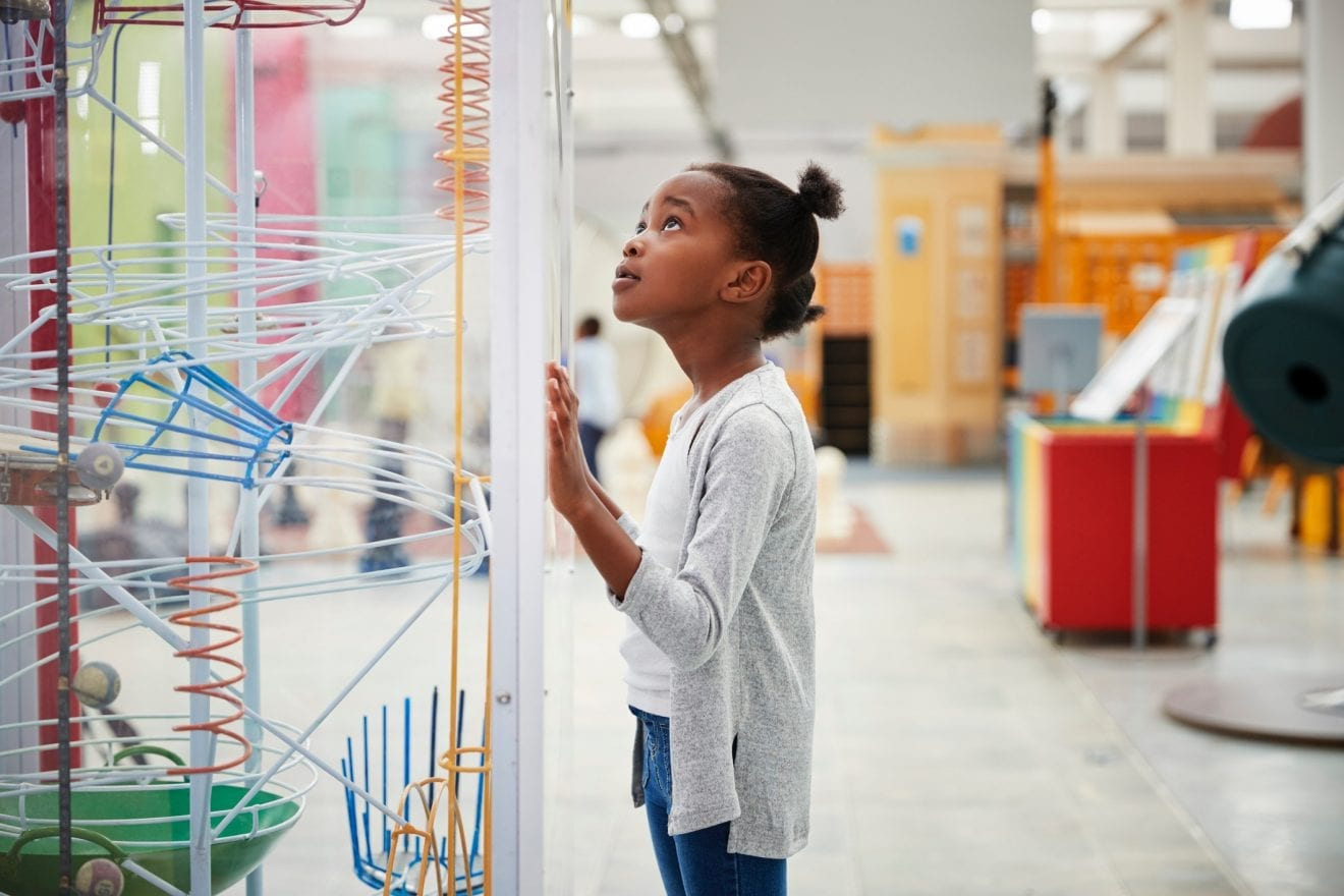 Young girl looking at a science exhibit, close up.