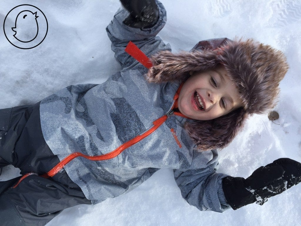 toddler smiling and laying on back in the snow