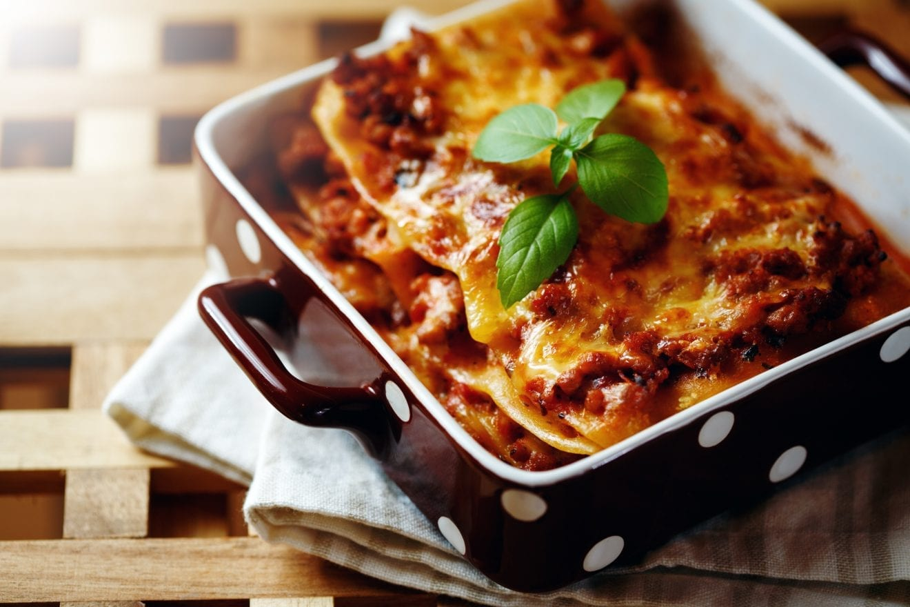 Italian Food. Hot Tasty Freshly Baked Lasagna Served with Basil Herb on Wooden Table.