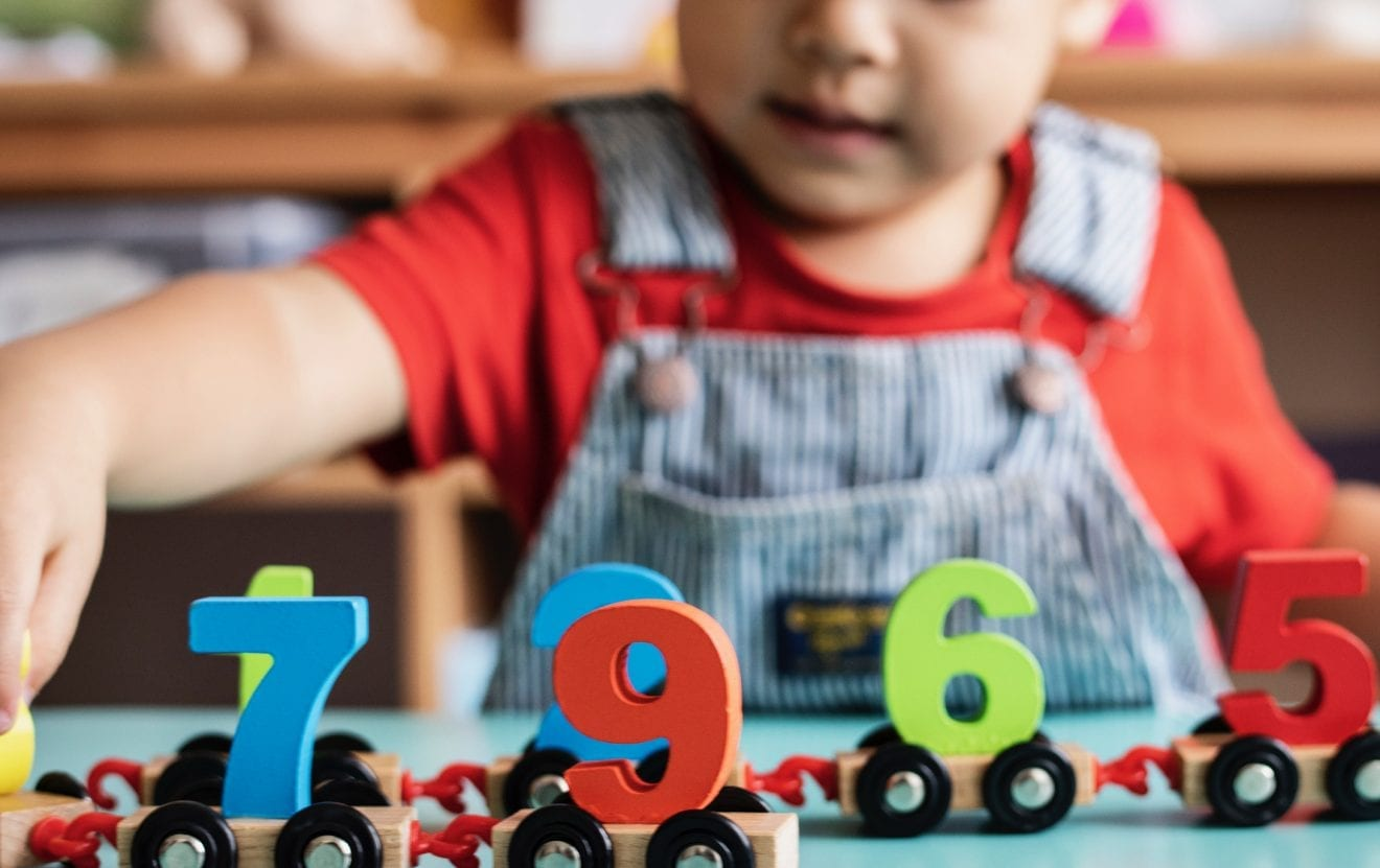 Little boy playing mathematics wooden toy at nursery