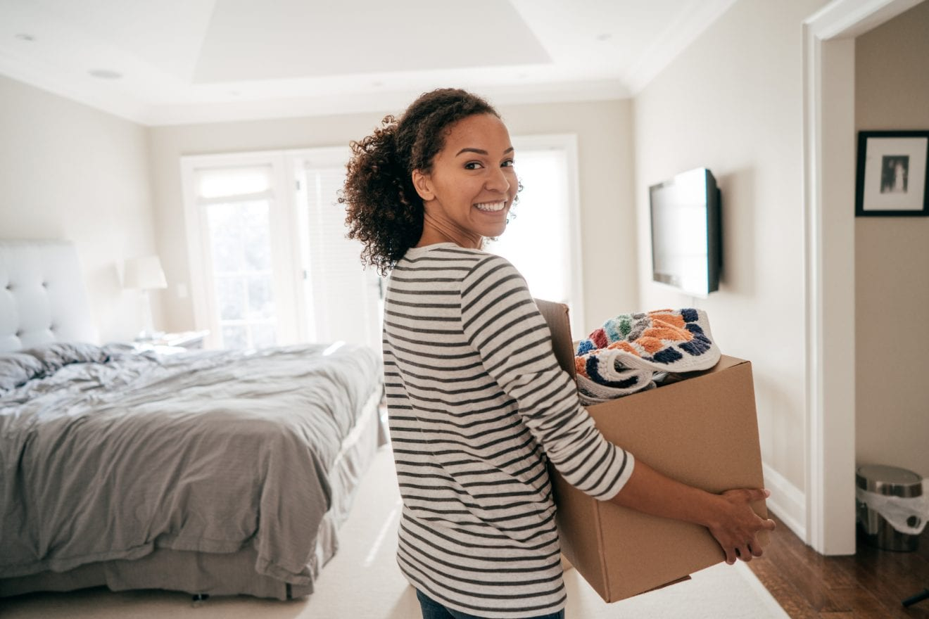 Woman holding a box full of things as she walks through her room.