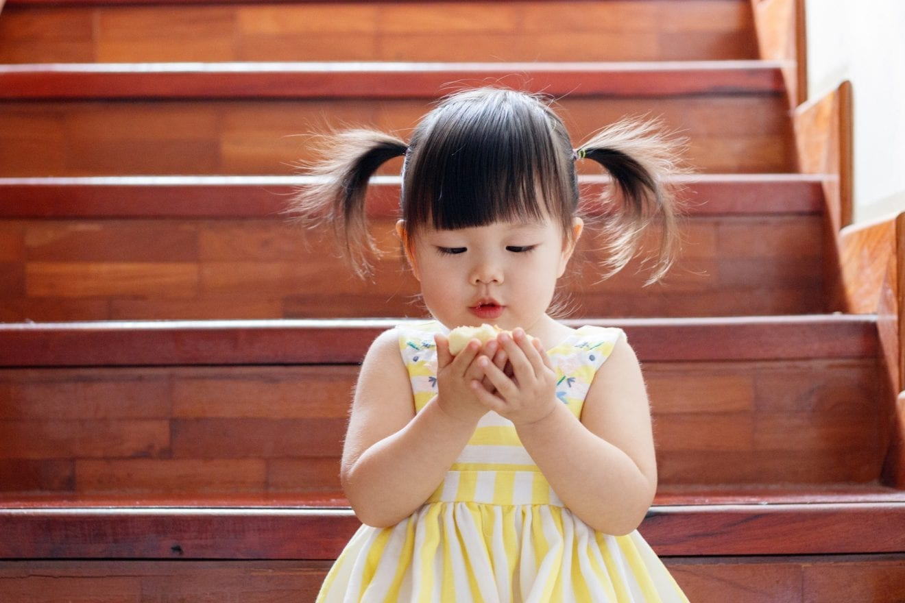 Little girl eating cup cake.