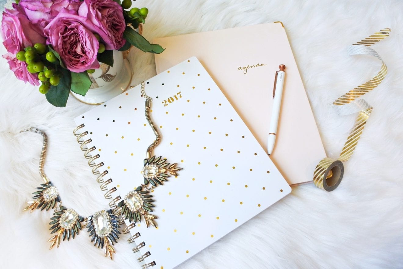 Agendas, washi tape, necklace and a mug with flowers on a sheepskin rug.