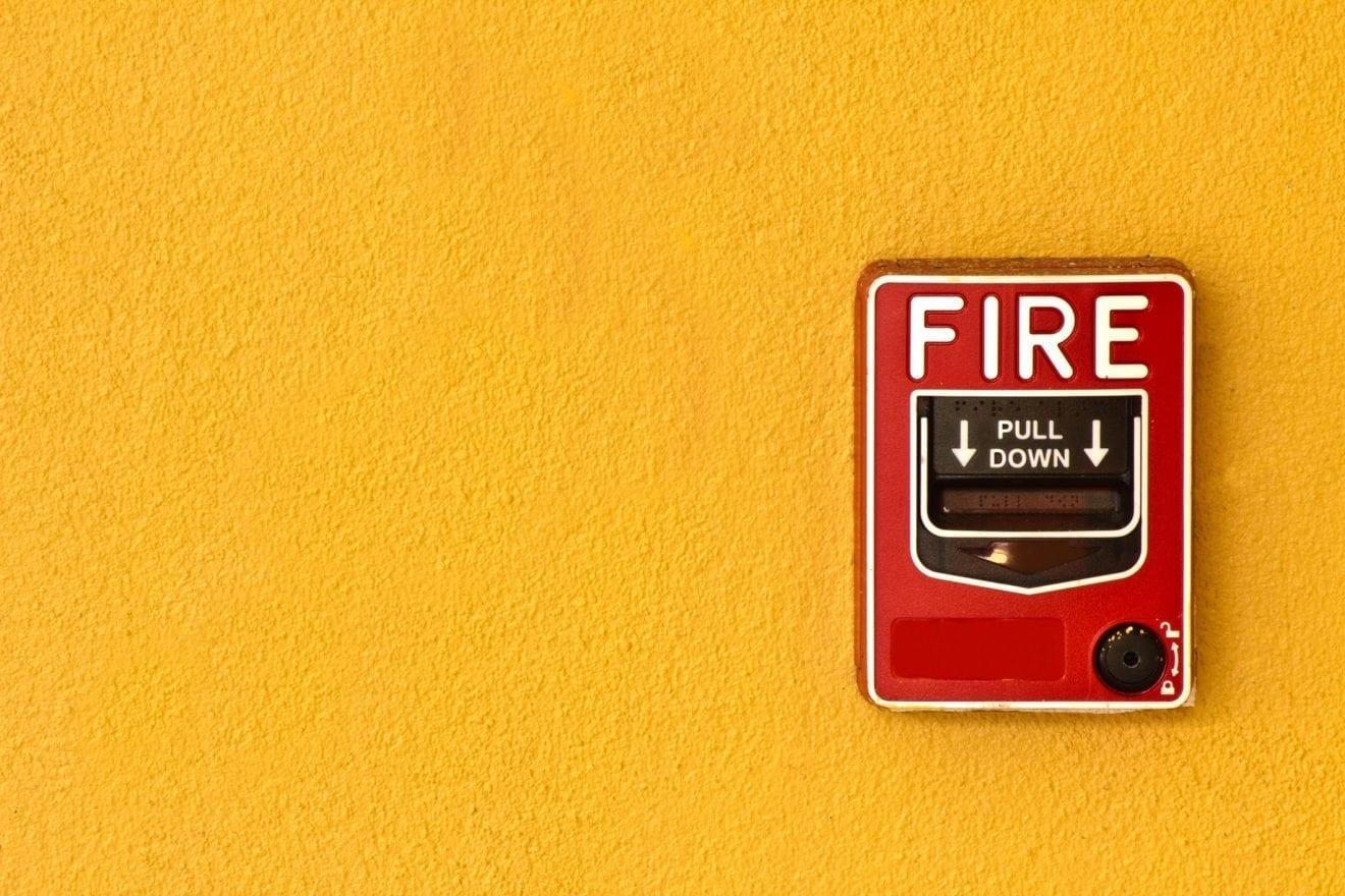 Fire break glass on yellow wall.