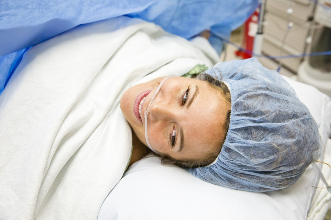 Mother smiling at view with her Newborn following surgery.