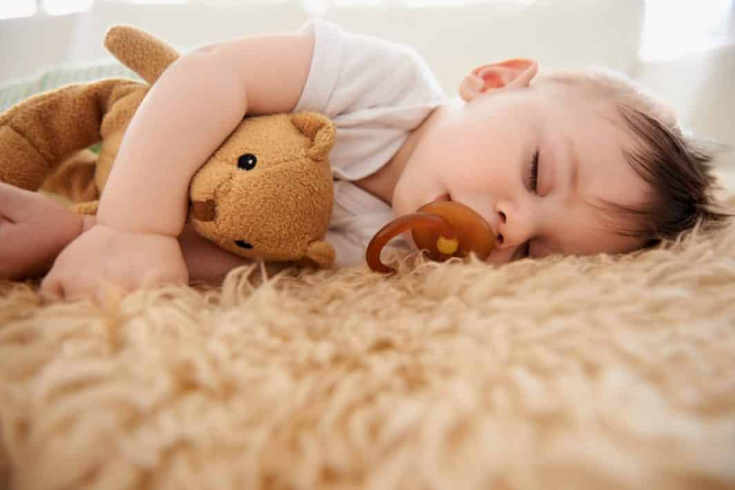 toddler sleeping on floor with pacifier in mouth
