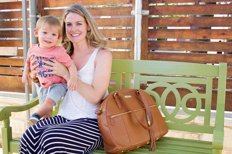 Mom sitting on a bench with diaper bag and holding a young toddler