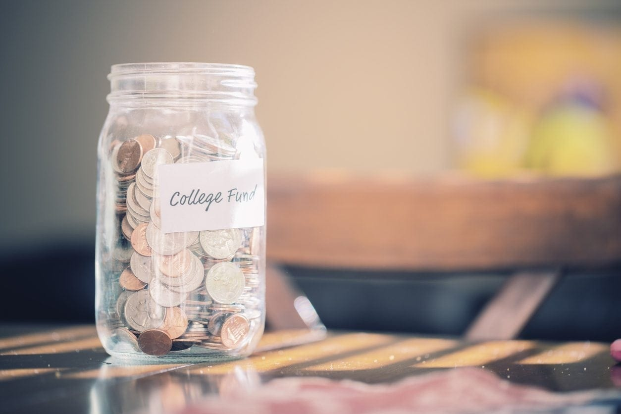 Glass jar labeled college fund filled with coins sitting on table.