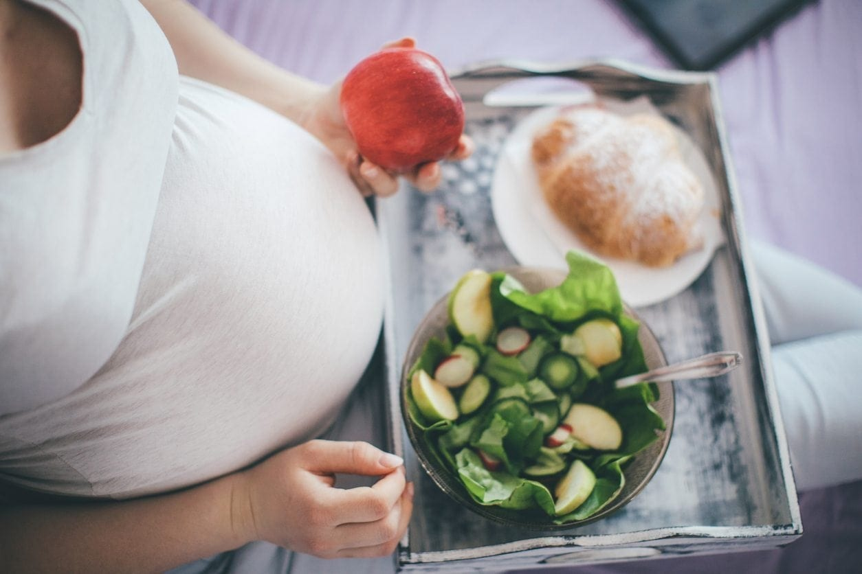 pregnant woman sitting with tray of food