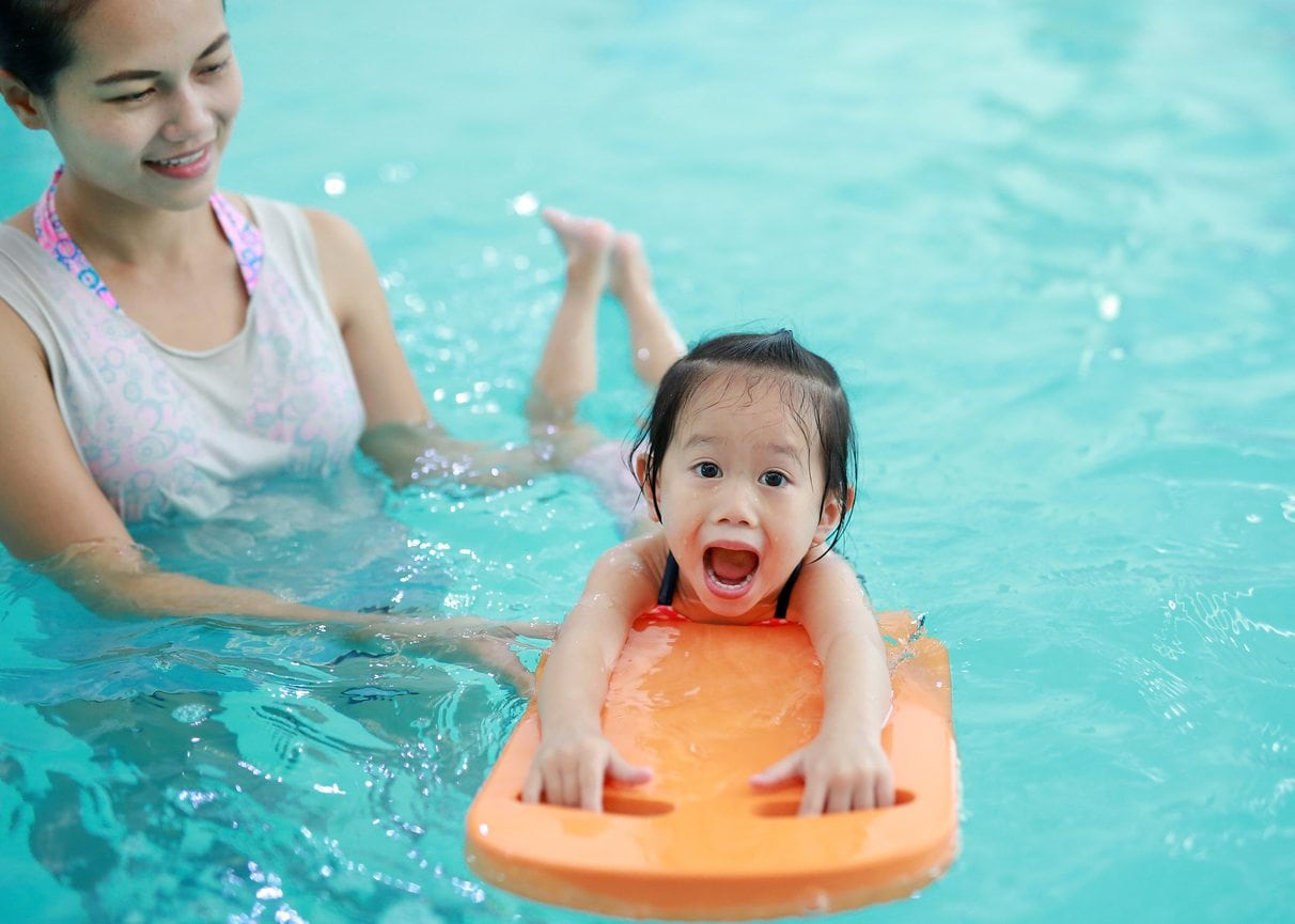 woman teaching toddler how to swim