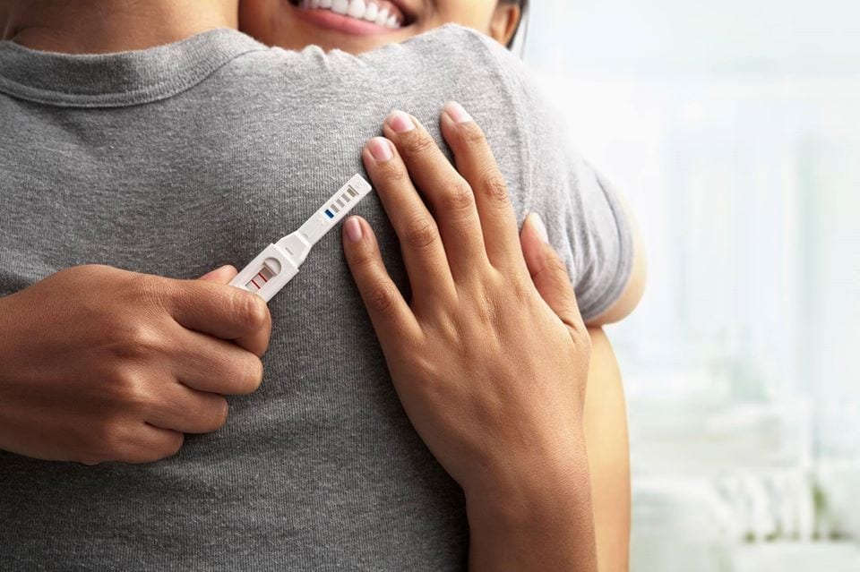 Woman hugging partner with a positive pregnancy test in her hand.