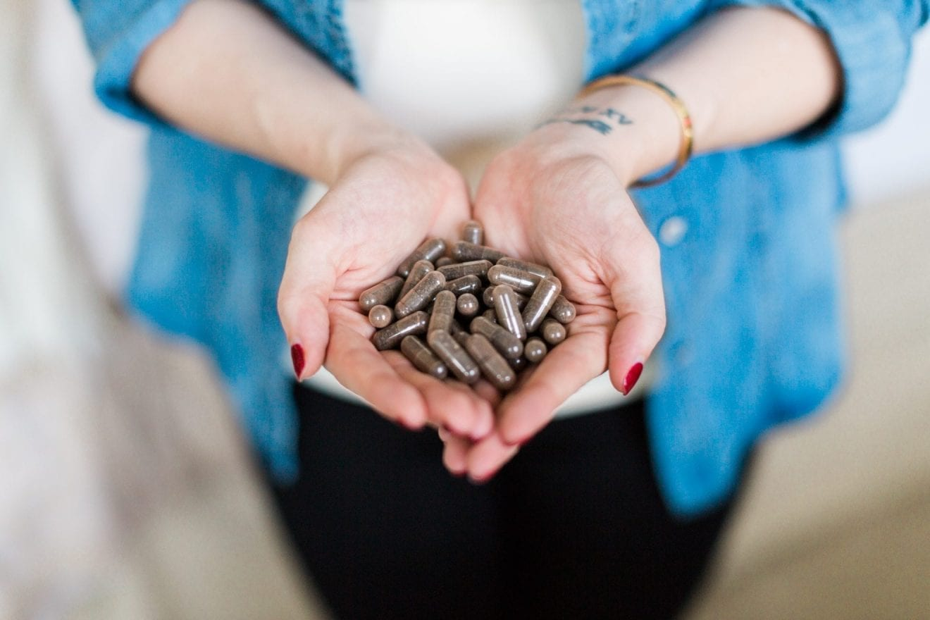 Woman holding in her hands encapsulated placenta pills.