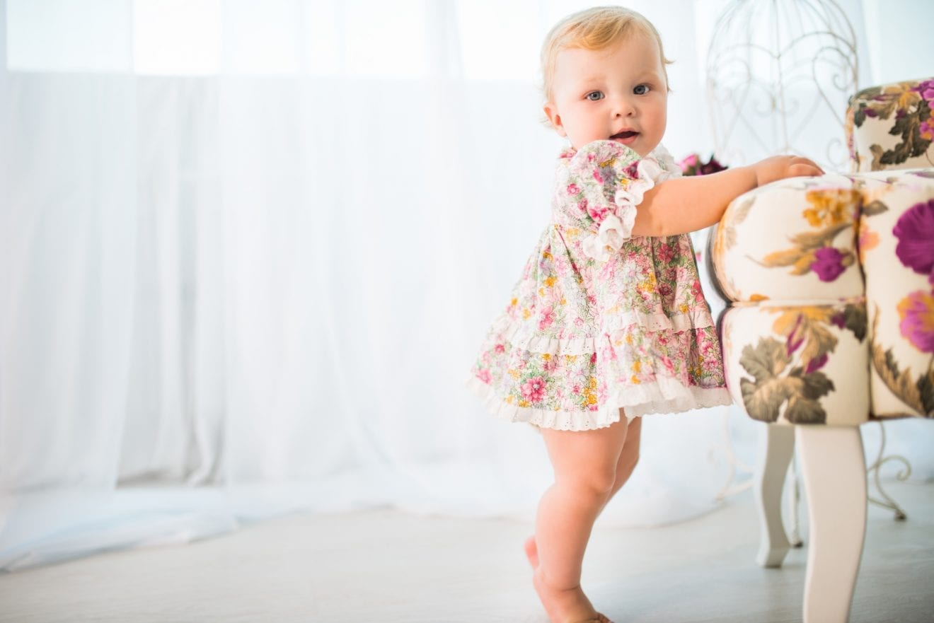 One year old girl taking first steps