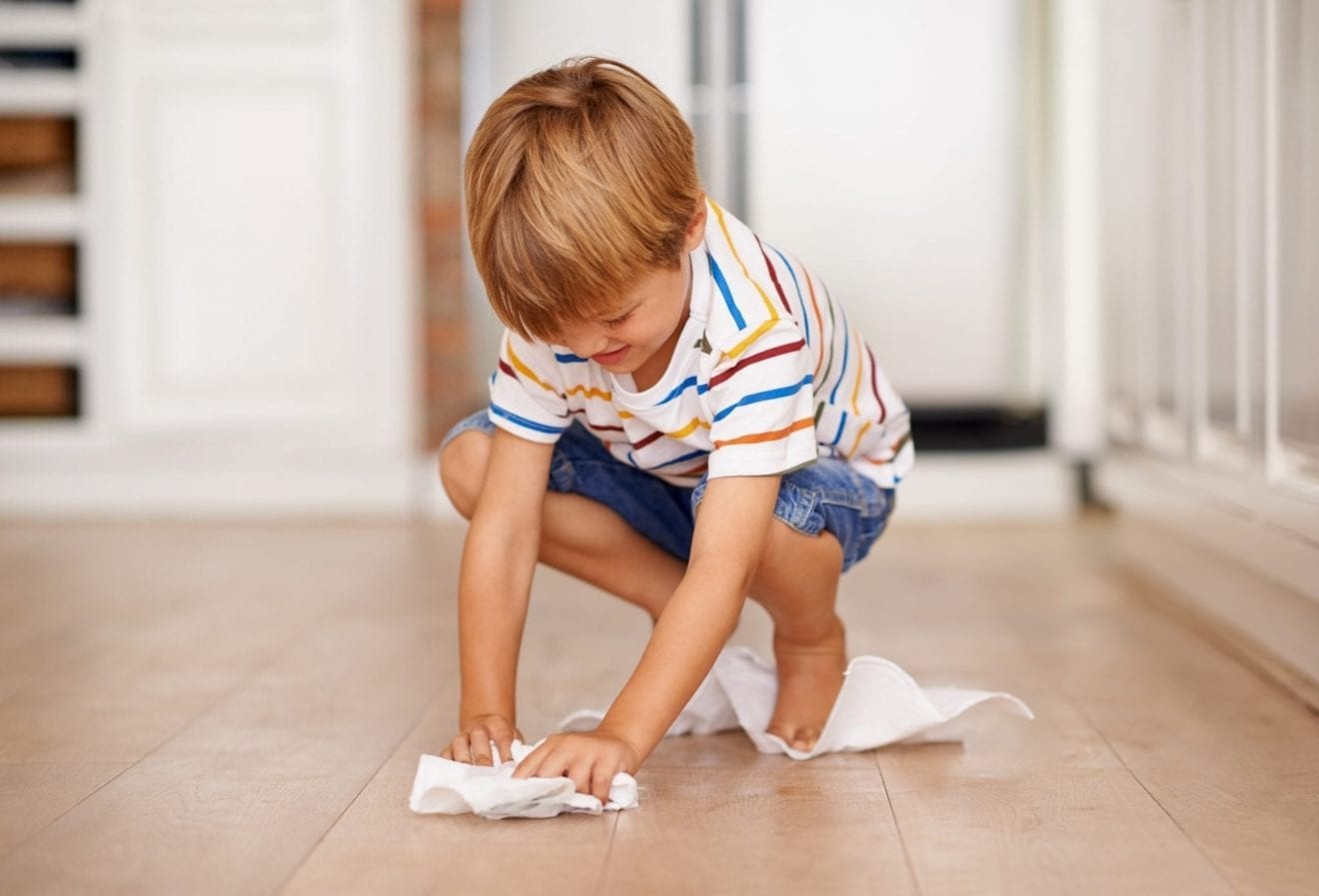 Little boy cleaning the floor with a paper towel