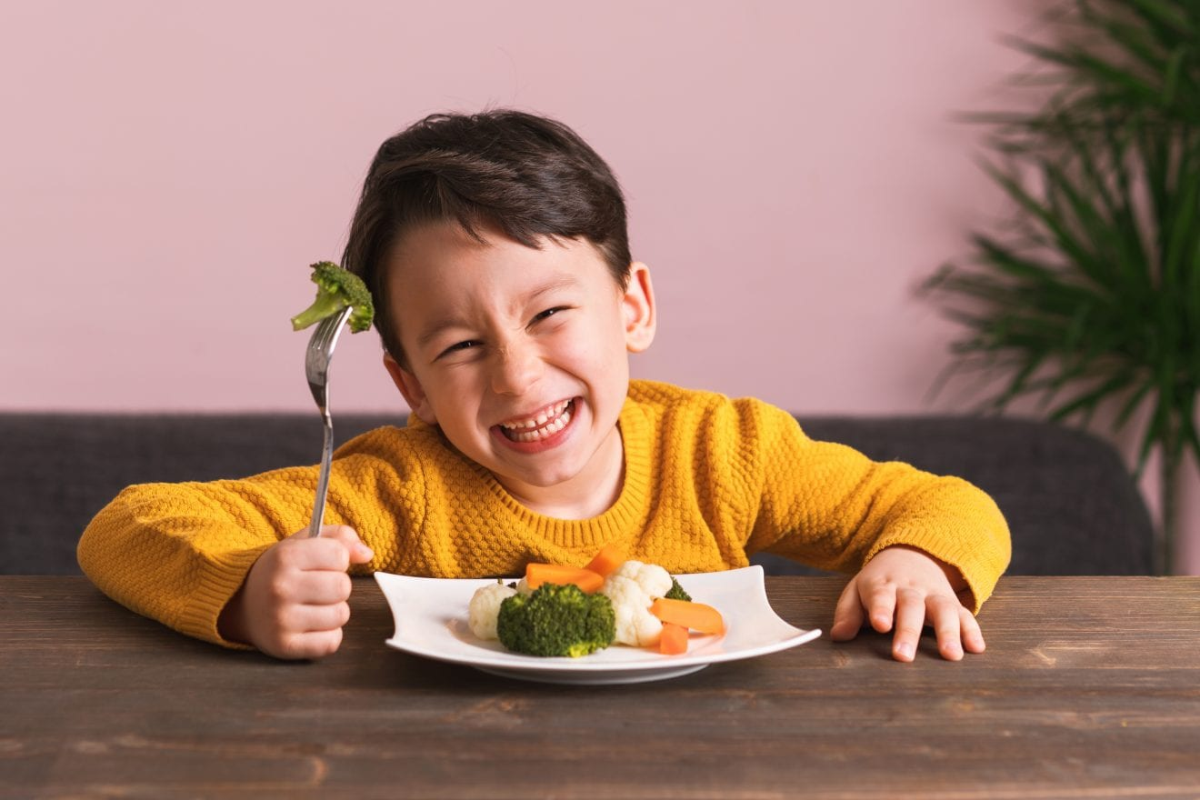 Happy child eating his vegetables.