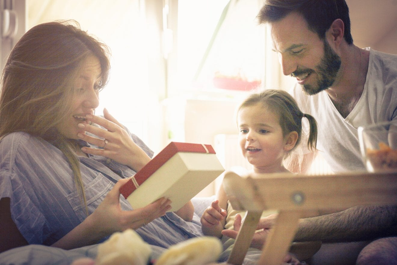 Family celebrating mother's day in bed while giving mom her Mother's Day gift.