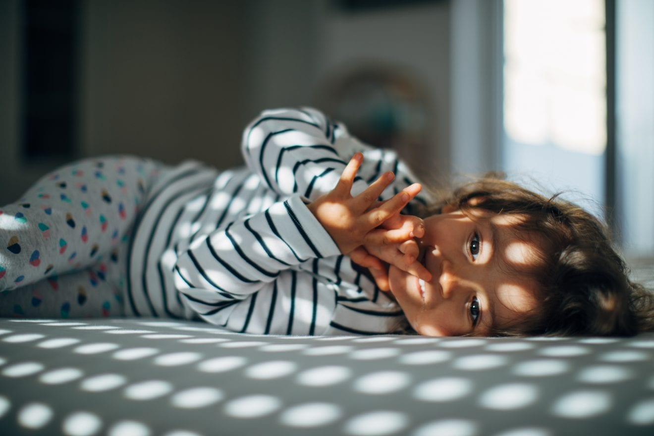 A little girl lying in bedroom bed alone on a beautiful morning.