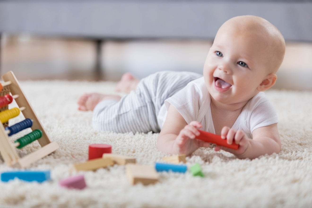 Cute baby sings with open mouth while playing with wooden blocks.