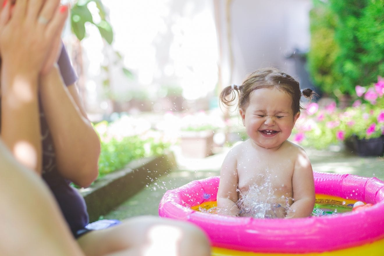 one year old baby girl is playing , splashing in the pool . baby is first time in pool and she is very happy and excited. mother is sitting beside her