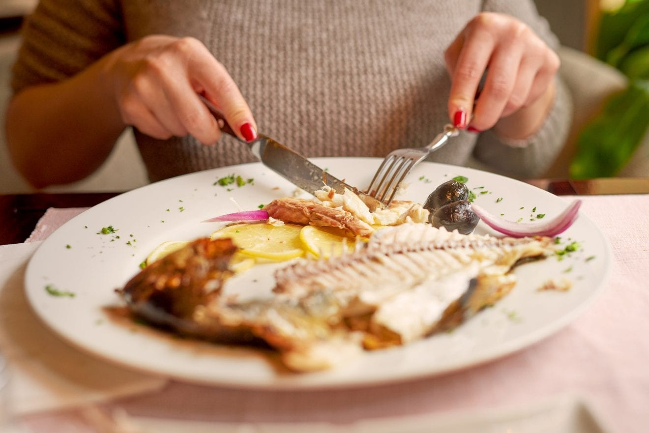 woman in restaurant eating fish, plate in front of her.