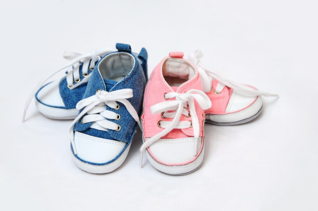Pink and blue baby shoes arrangement.