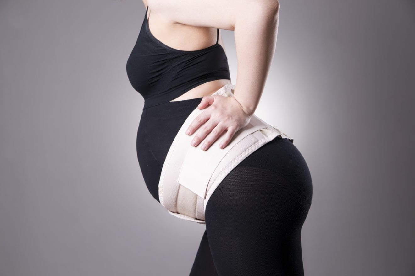 Young caucasian pregnant woman with pregnancy support belt