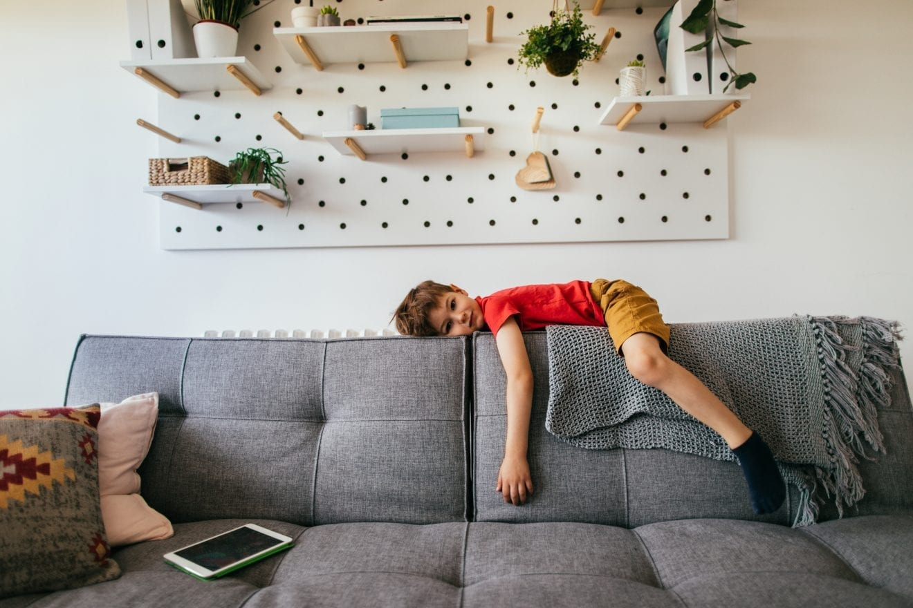 Photo of a little boy who is being bored, lying down on the sofa in his living room.