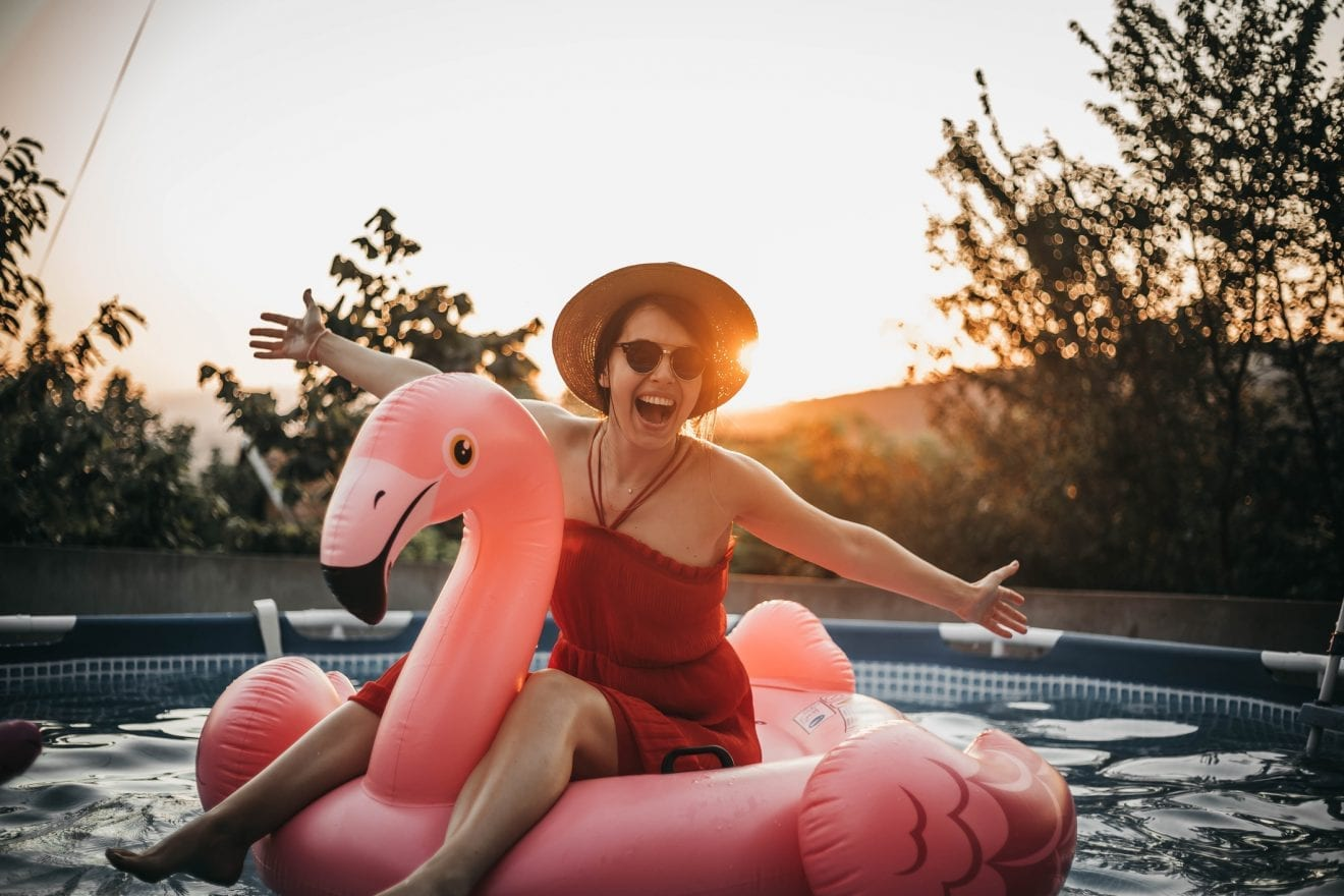 Mom in the pool sitting on an inflatable flamingo pool floatie