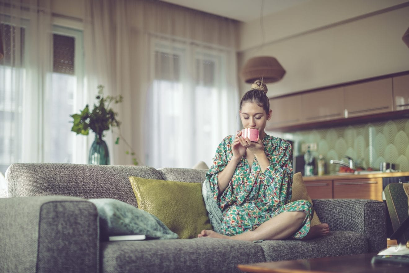 Young woman at home sitting on her couch drinking coffee in her robe.