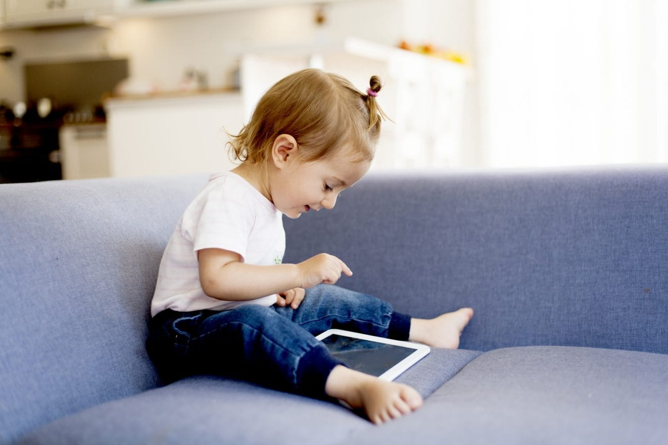 Cute little girl sitting on the couch using a digital tablet.