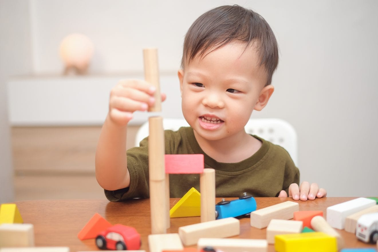 Cute little Asian toddler boy child having fun playing with wooden building block toys.