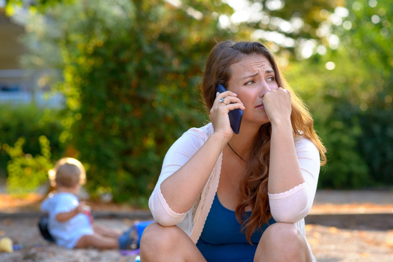 Stressed depressed young mother talking on a mobile phone as she sits outside in a playground with her baby son playing behind her.