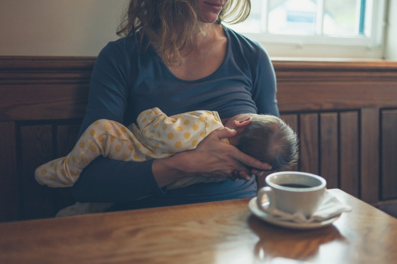 A young mother is breastfeeding her baby in a cafe while she is having a coffee.