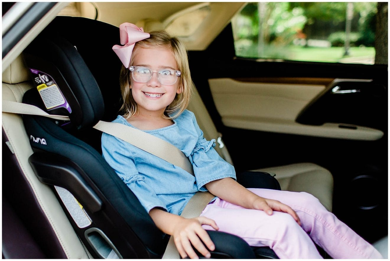 Young girl sitting in her NUNA EXEC all-in-one car seat.