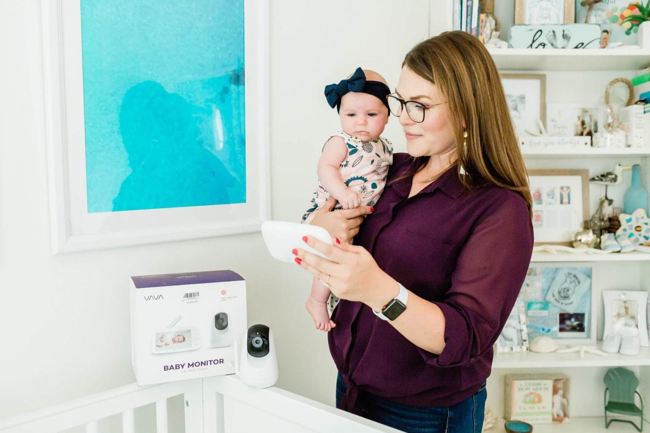 Mom holding her daughter as she is looks at the VAVA baby monitor.