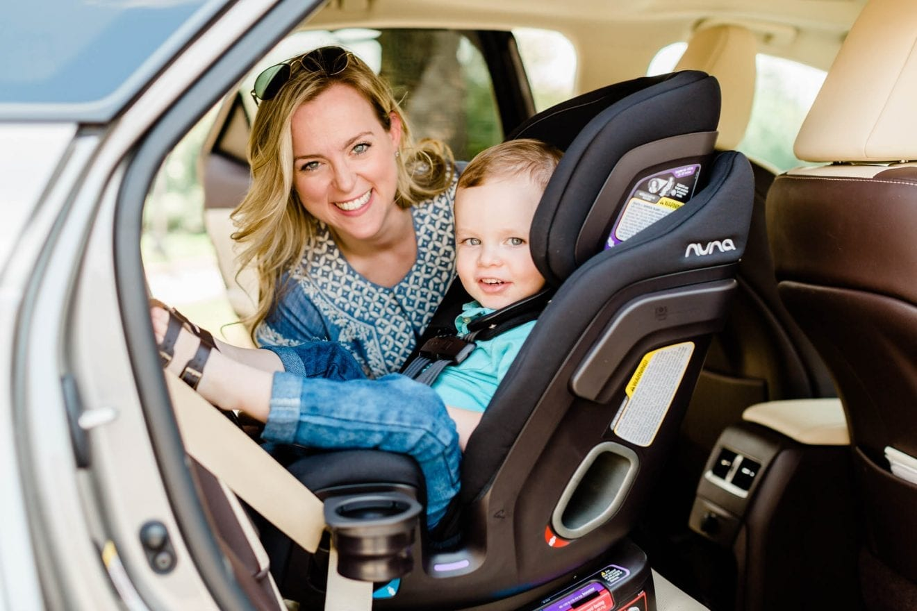 Toddler boy sitting in his all-in-one NUNA EXEC carseat with his mom helping him buckle in.