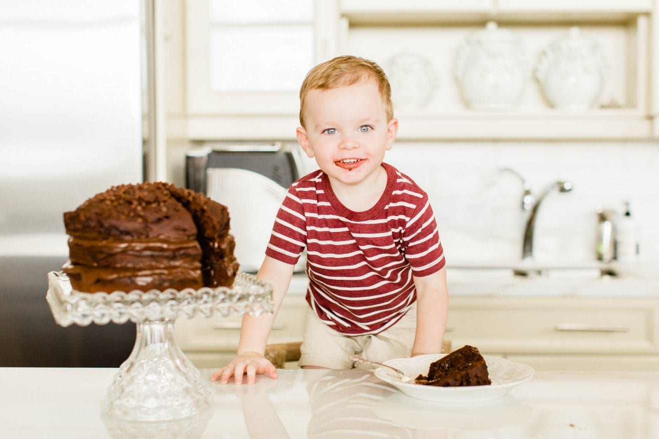 Toddler boy standing by a chocolate cake with some chocolate on his face.