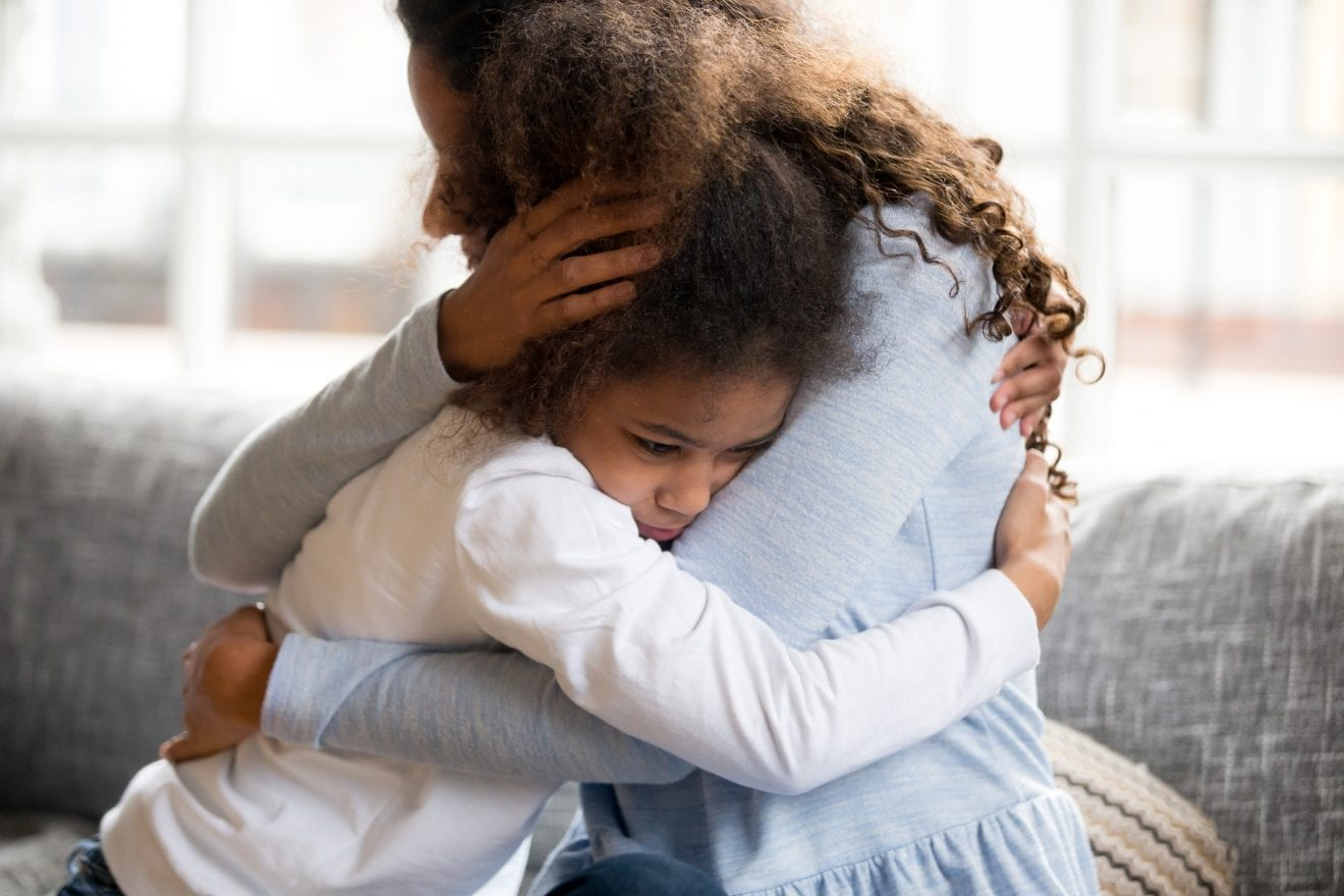 Black African mother embrace little preschool frustrated kid sitting on couch together at home. American loving mother supports disappointed daughter sympathizing, making peace after scolding concept.