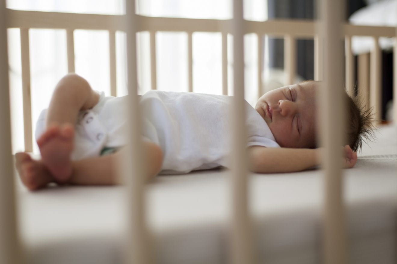 Cute baby sleeping on her back inside her crib.