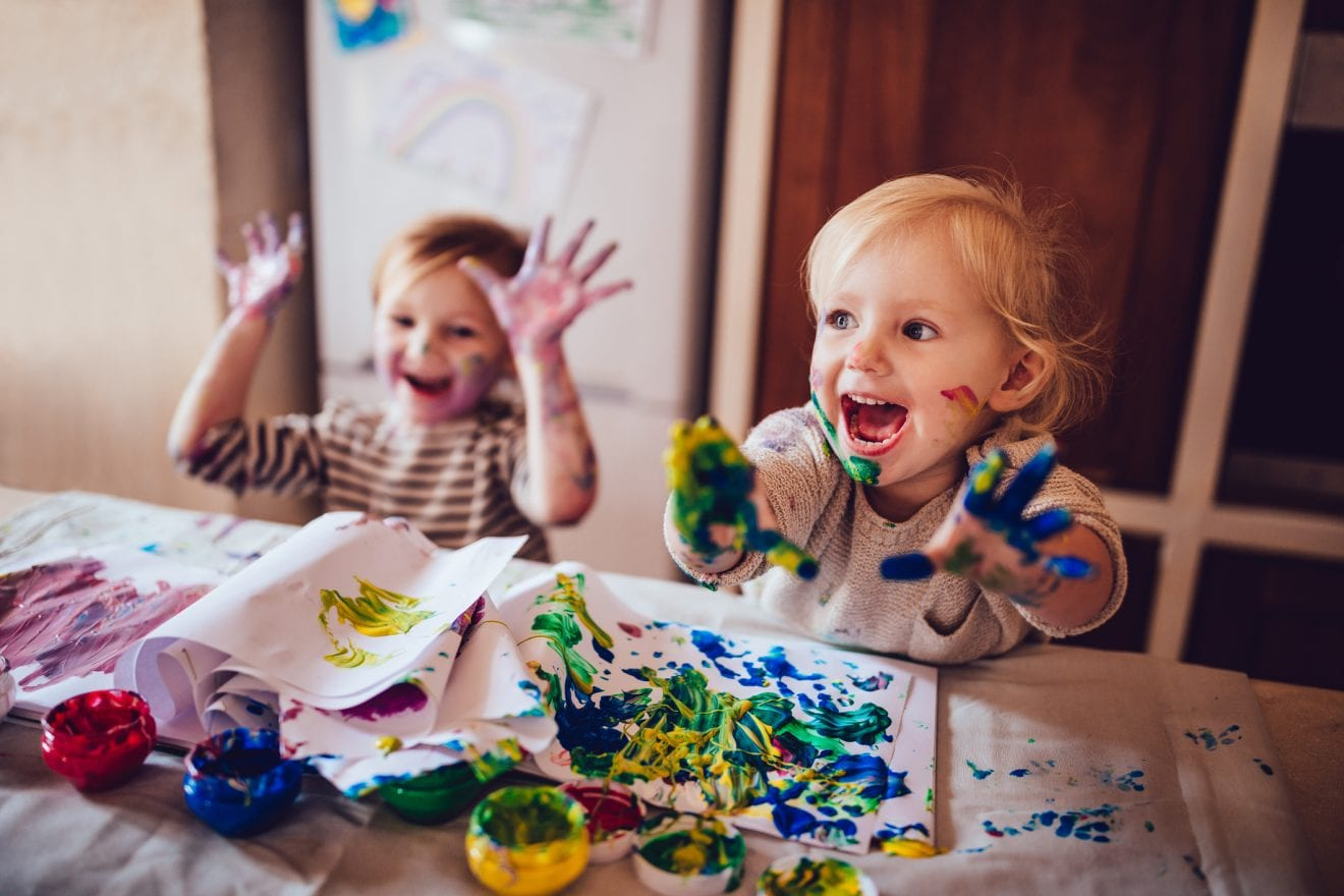 Happy little girls with dirty hands and faces having fun being creative with finger painting.
