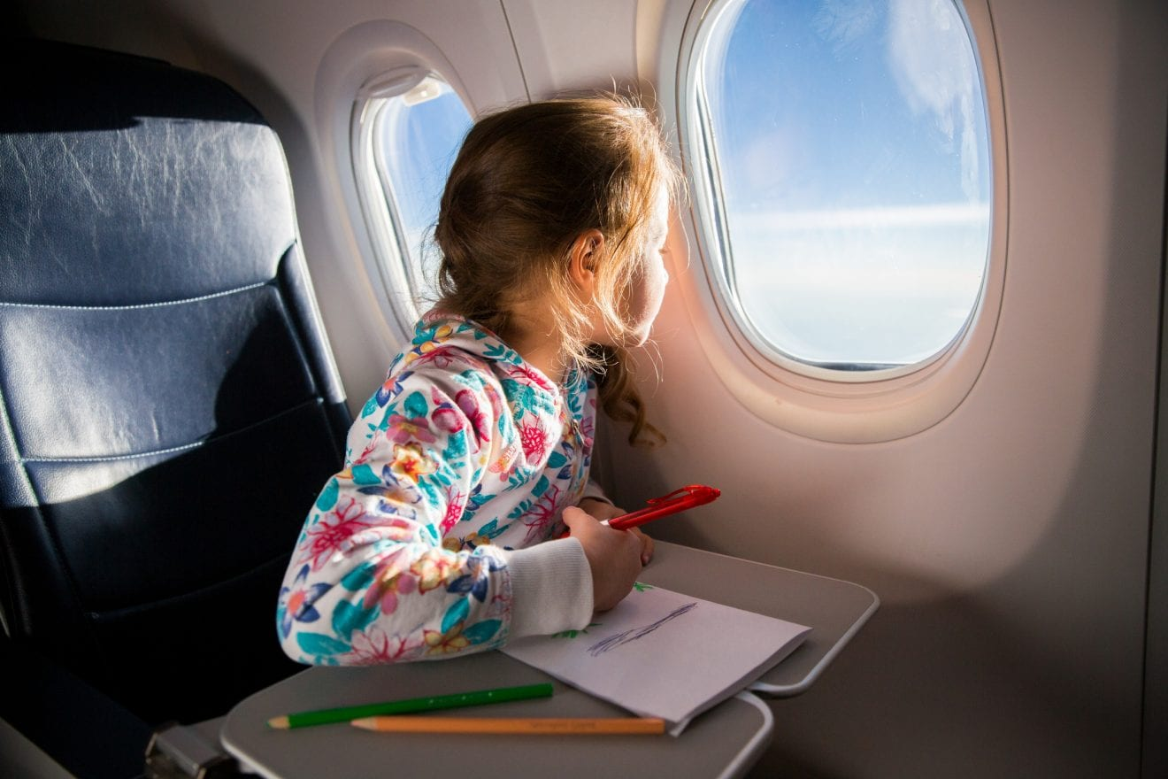 Child drawing picture with crayons in airplane. Little girl occupied while flying in aircraft. Travel with family and kids. Blue sky and sun outside the window.