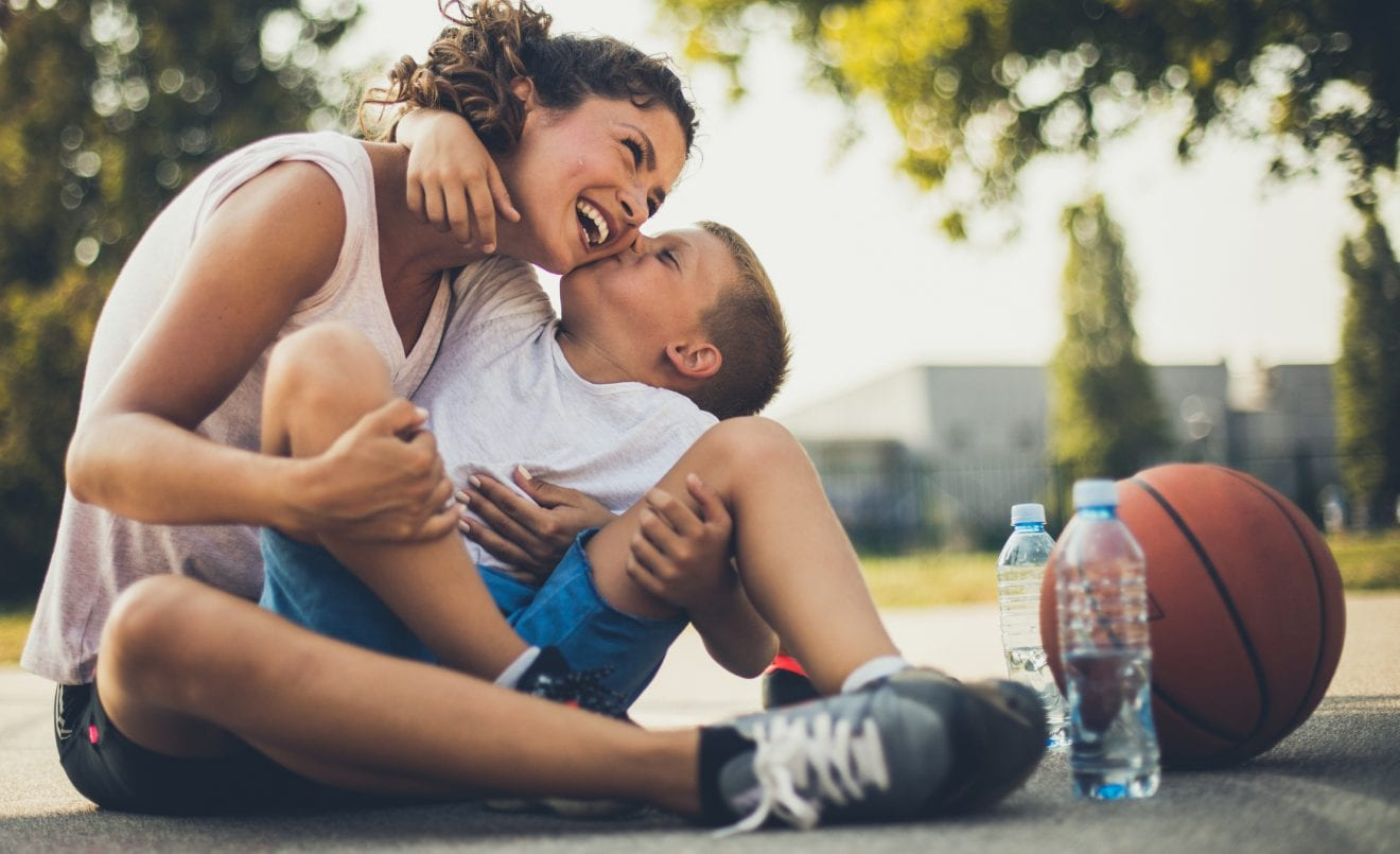 The most valuable kiss in the world. Mother and son on playground. Close up.