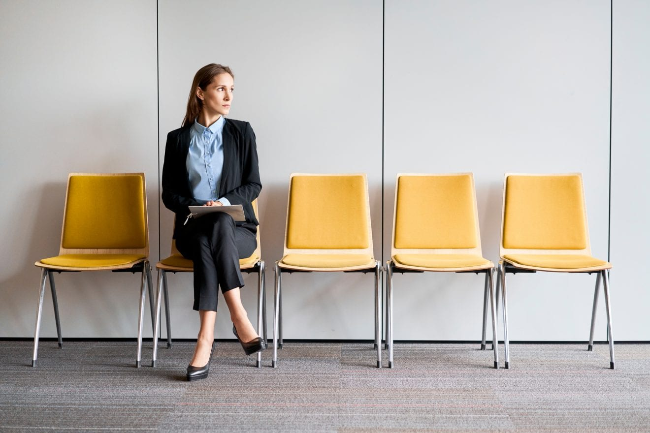 Young woman sitting in lobby with resume in hands and waiting for job interview.