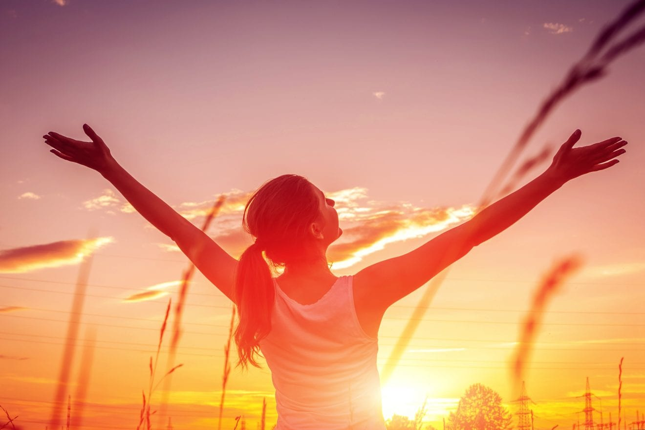 Free and happy woman raises arms against the sunset sky. Harmony and balance concept.