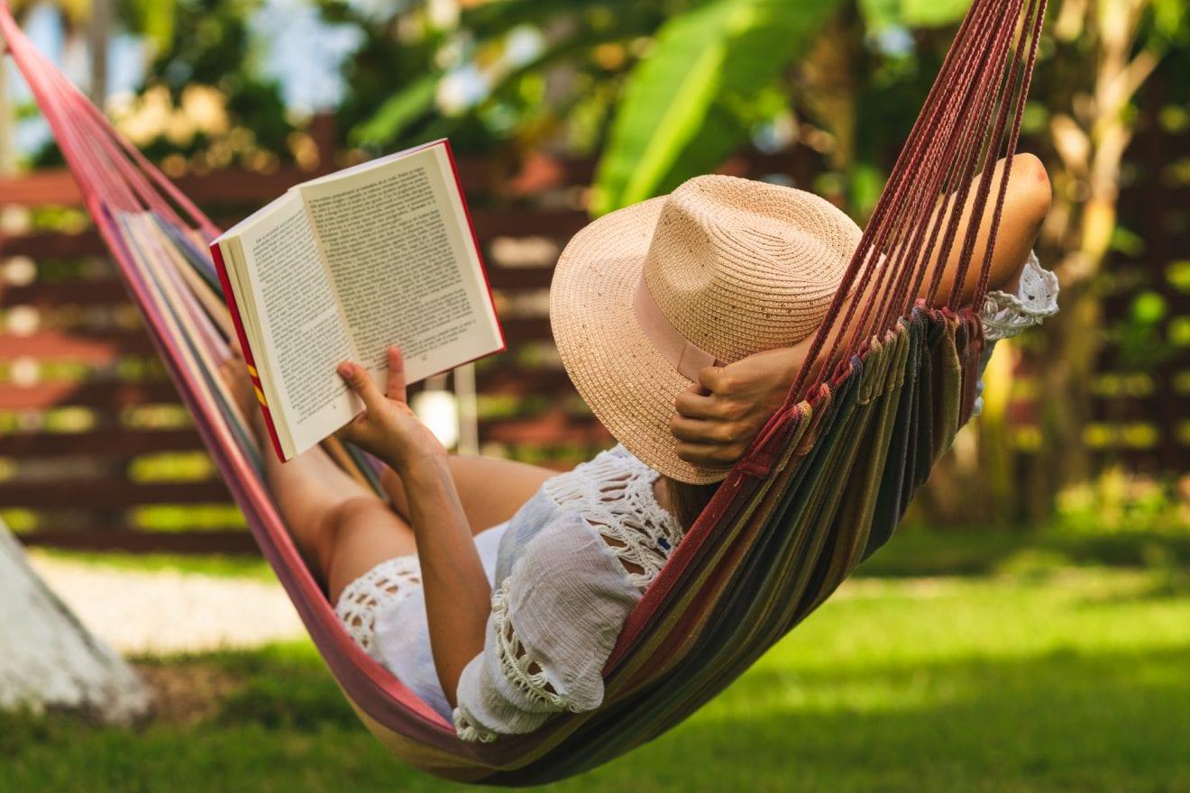 Happy woman in white dress relaxing in hammock reading a book.